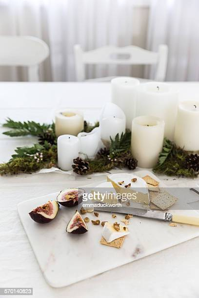 Cheese platter next to a candle centerpiece on dining room table