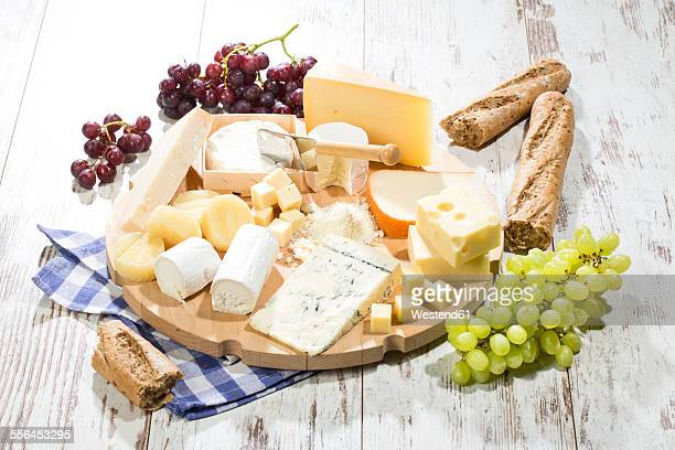 Cheese platter with different sorts of cheese, baguette and grapes on wood