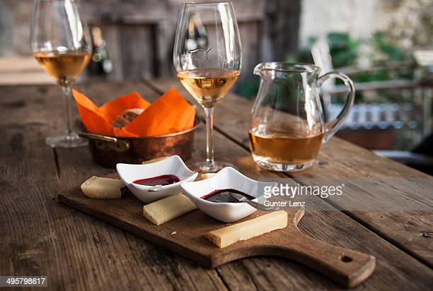 Cheese platter with dips, bread basket, wine glasses and wine jug, Tirano, Sondrio province, Lombardy, Italy