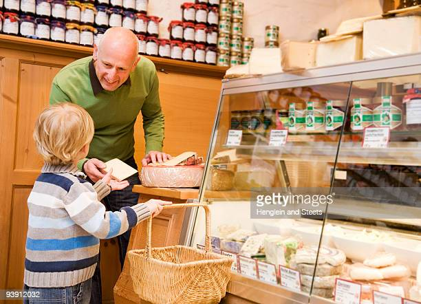cheese store owner with boy in shop