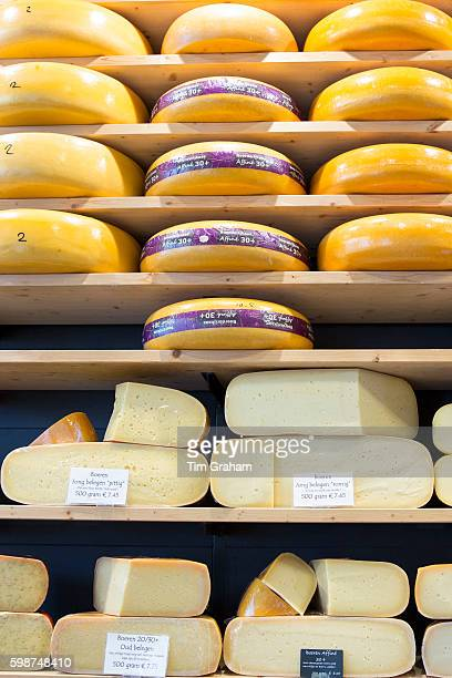 Cheese wheels and wedge on display shelves at traditional cheese shop 't Kaaswinkeltje in Gouda The Netherlands