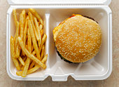 Cheeseburger and french fries in take-out container