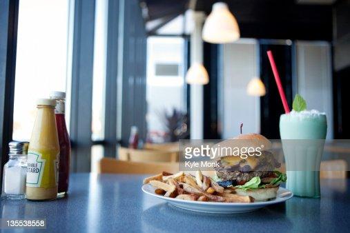 Cheeseburger, french fries and milkshake in diner