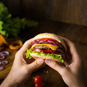 Cheeseburger. Man hands holding burger with cheese, red onion, tomatoes, lettuce green salad and pickles. Square crop. Closeup view, selective focus