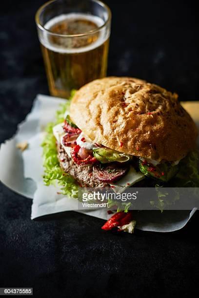 Cheeseburger on greaseproof paper, beer glass