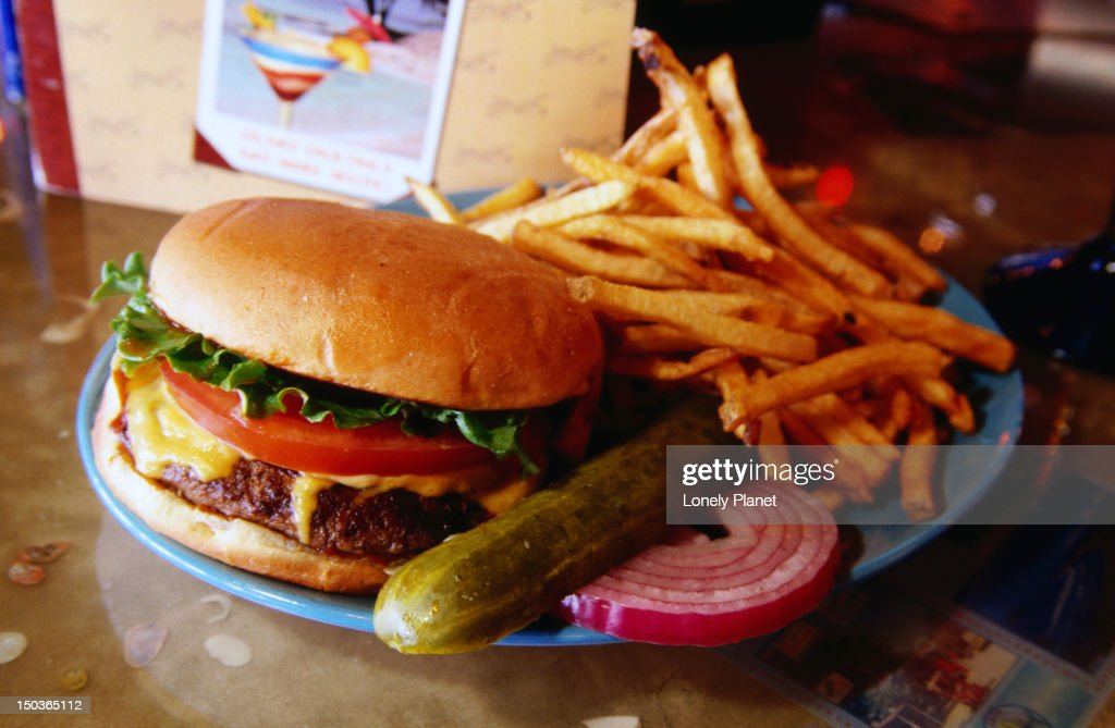 Cheeseburger platter with pickle and french fries, Cheeseburger in Paradise restaurant, Village West area. : Stock Photo