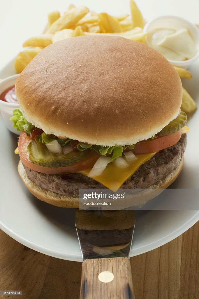 Cheeseburger with accompaniments on plate : Stock Photo