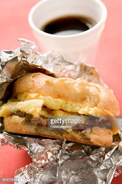 Cheeseburger with scrambled egg, a bite taken; coffee cup