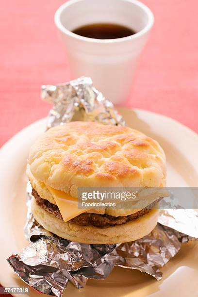 Cheeseburger with scrambled egg on aluminium foil, coffee cup
