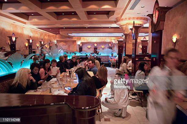 A Cheesecake Factory waiter takes a patron's order at a restaurant in Denver Colorado US on Friday March 11 2011 Americans are back to eating out at...