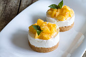 Mini cheesecake with peaches on wooden background.