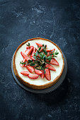 Cheesecake with fresh strawberries and eucalyptus leaf over dark slate stone background. High angle view