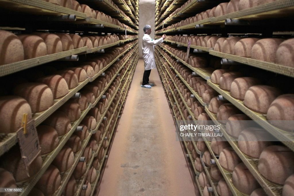 A cheesemonger checks mimolette cheese at a production site of the French Isigny Ste Mere company on July 4, 2013 in Isigny-sur-Mere, northwestern France. After more than a tonne of mimolette cheese has been held up in customs for 3 months, US officials have effectively banned the French speciality, calling it putrid and unfit for food. Since March, several hundred pounds of the bright orange cheese have been held up by US customs because of a warning by the Food and Drug Administration that it contained microscopic cheese mites. The mites are a critical part of the process to produce mimolette, giving it its distinctive grayish crust.