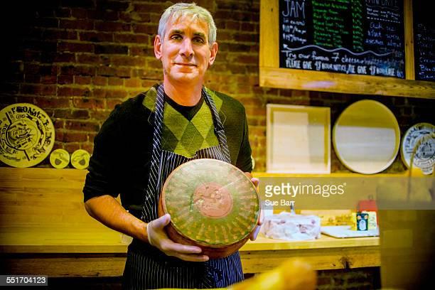 Cheesemonger holding wheel of cheese