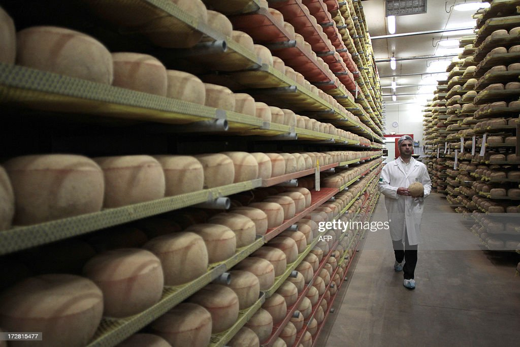 A cheesemonger walks along mimolette cheese in a production site of the French Isigny Ste Mere company on July 4, 2013 in Isigny-sur-Mere, northwestern France. After more than a tonne of mimolette cheese has been held up in customs for 3 months, US officials have effectively banned the French speciality, calling it putrid and unfit for food. Since March, several hundred pounds of the bright orange cheese have been held up by US customs because of a warning by the Food and Drug Administration that it contained microscopic cheese mites. The mites are a critical part of the process to produce mimolette, giving it its distinctive grayish crust. AFP PHOTO CHARLY TRIBALLEAU