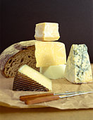 Cheeses and bread on block with knives