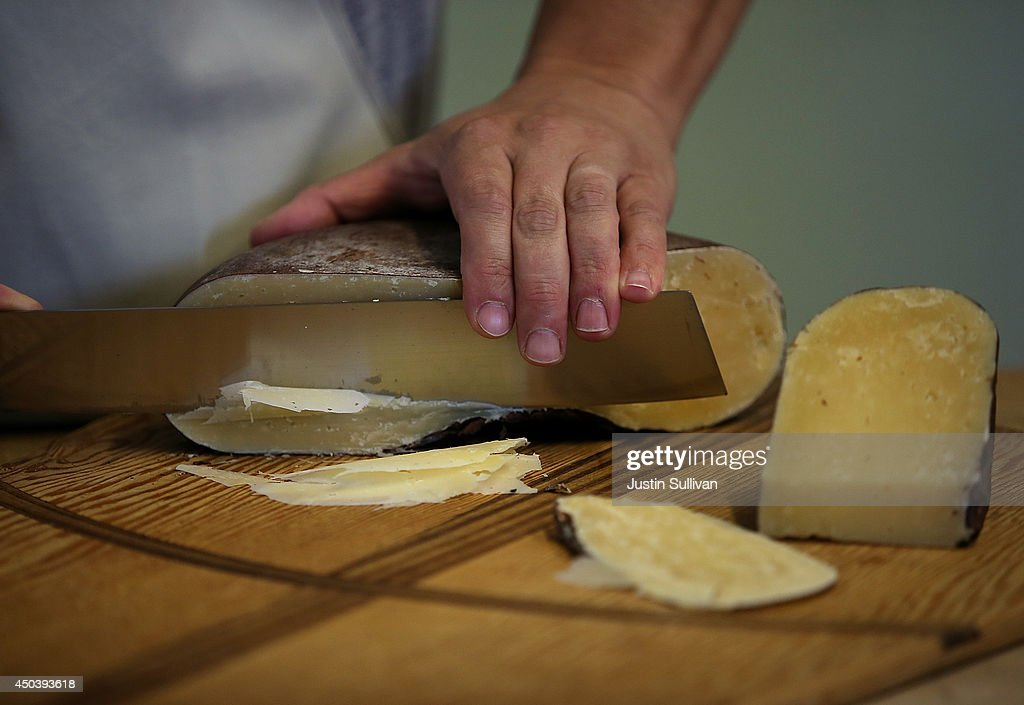 Cheesmaker Gabriel Luddy cuts a wheel of dry aged jack cheese at Vella Cheese on June 10 2014 in Sonoma California The Food and Drug Administration...