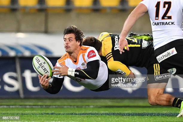 Cheetahs' captain Francois Venter passes the ball while being tackled by Hurricanes' Wes Goosen during the Super Rugby match between New Zealand's...