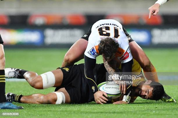 Cheetahs' captain Francois Venter tries to take the ball from Hurricanes' Vaea Fifita during the Super Rugby match between New Zealand's Hurricanes...