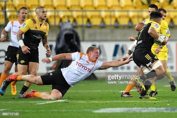 Cheetahs' Elandre Huggett misses a tackle on Hurricanes' Ardie Savea during the Super Rugby match between New Zealand's Hurricanes and South Africa's...