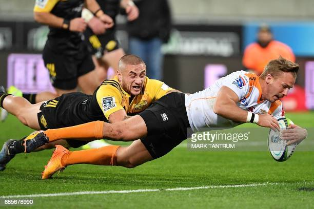 CORRECTION Cheetahs' Fred Zeilinga scores while Hurricanes' captain TJ Perenara chases during the Super Rugby match between New Zealand's Hurricanes...