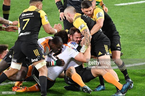 Cheetahs' Niel Marais attempts to get the ball down over the try line while Hurricanes' captain TJ Perenara holds it up during the Super Rugby match...