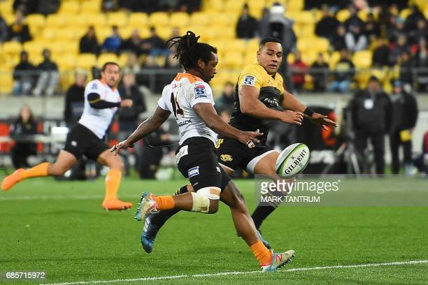 Cheetahs' Sergeal Petersen and Hurricanes' Ngani Laumape fight for the ball during the Super Rugby match between New Zealand's Hurricanes and South...