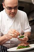 Chef Adding Seasoning To Dish In Restaurant Kitchen