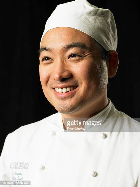 Chef against black background, head and shoulders, portrait