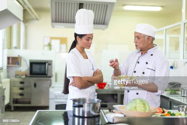 Chef and assistant preparing asian food in restaurant's kitchen