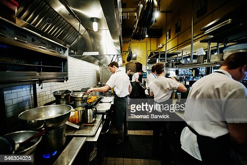 Restaurant Kitchen Staff chef and kitchen staff discussing food preparation stock photo