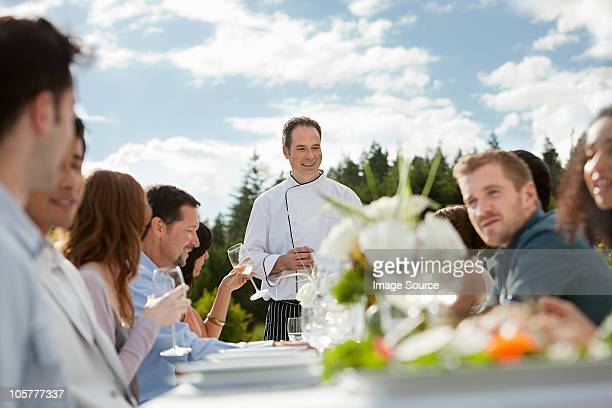 Chef and people at outdoor dinner party