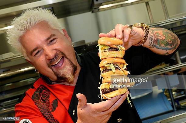 Chef and television personality Guy Fieri holds hamburgers in the kitchen during a welcome event for Guy Fieri's Vegas Kitchen Bar at The Quad Resort...