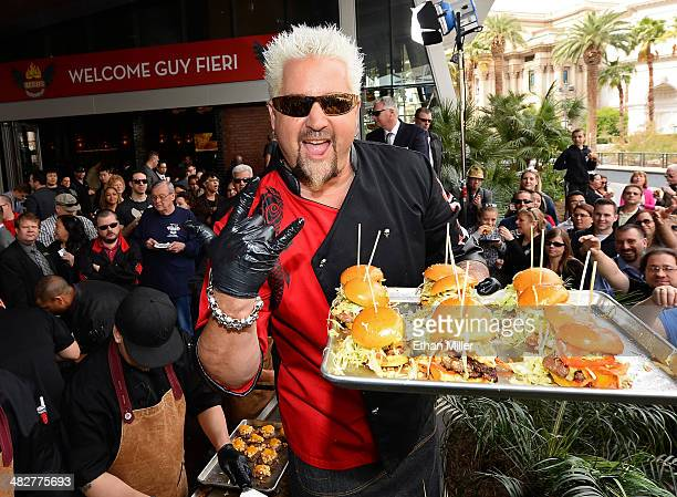 Chef and television personality Guy Fieri poses as he serves hamburgers to guests during a welcome event for Guy Fieri's Vegas Kitchen Bar at The...