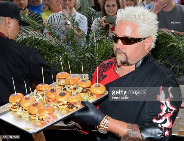 Chef and television personality Guy Fieri serves hamburgers to guests during a welcome event for Guy Fieri's Vegas Kitchen Bar at The Quad Resort...