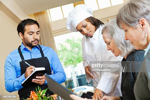 Chef and waiter helping customers in restaurant order