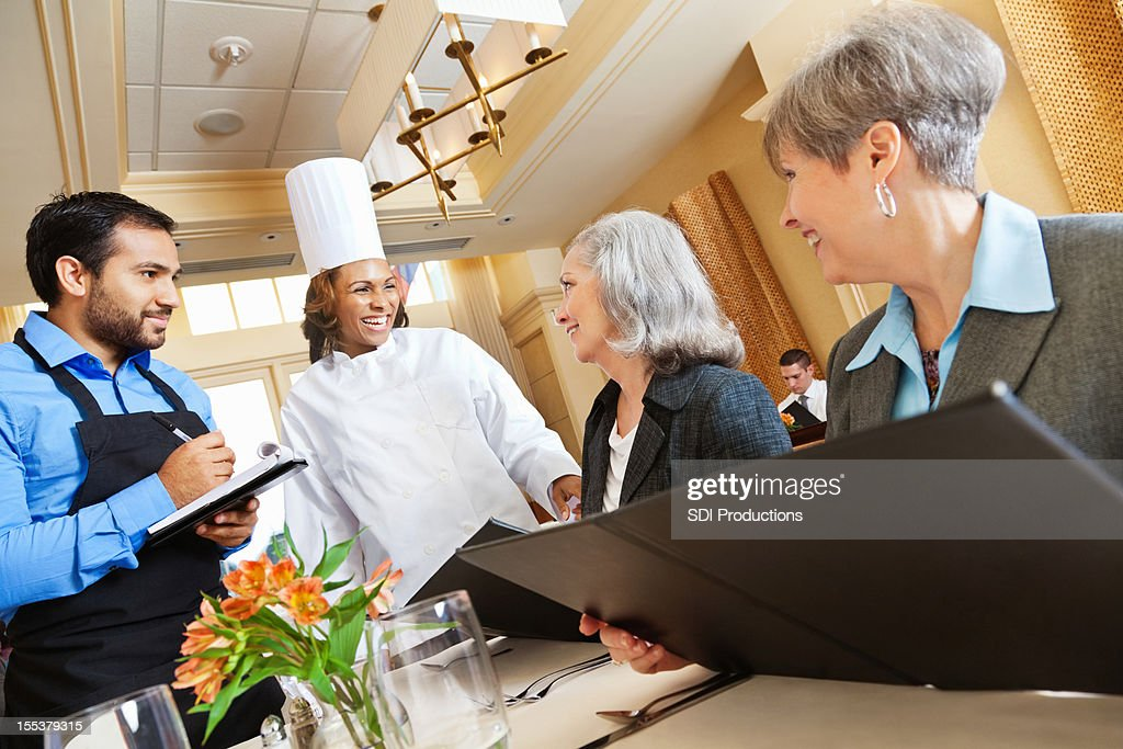 Chef and waiter laughing with customers while making menu suggestions : Stock Photo