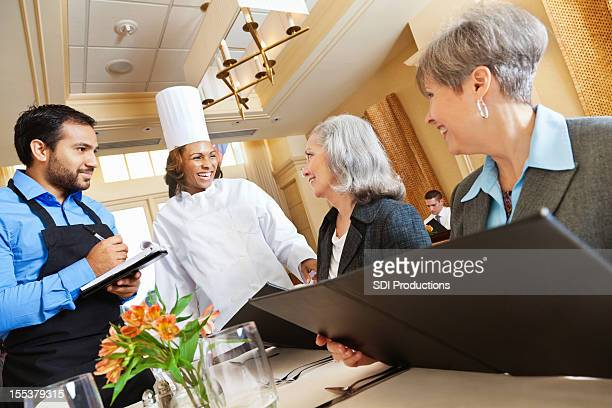 Chef and waiter laughing with customers while making menu suggestions