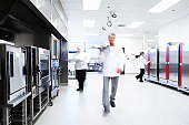 Chef and waiters carrying food in restaurant kitchen (blurred motion)