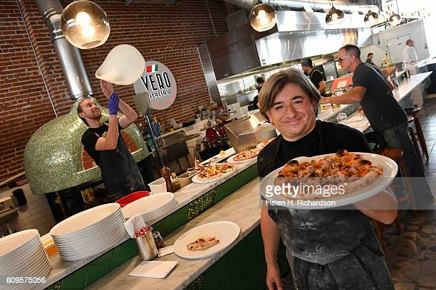 Chef Andrea Frizzi owner of Vero Italian right shows off one of his pizzas as Shane Burton general manager left tosses dough in the air at their new...