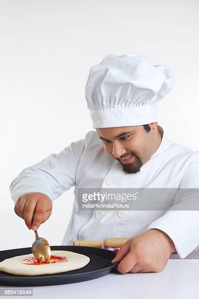 Chef applying topping on pizza dough