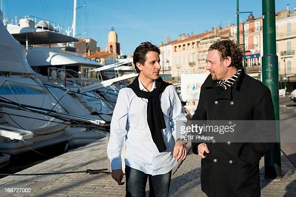 Chef Arnaud Donckele with Thierry Di Tullio the dinning room director look for a painting on the port on March 21, 2013 in Saint Tropez,France. Chef of the restaurant La Vague D'Or in the hotel La Residence de la Pinede who received his 3rd star from the famous gourmet guide Michelin.