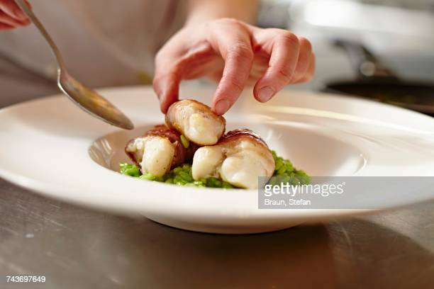 A chef arranging fish in bacon on a plate