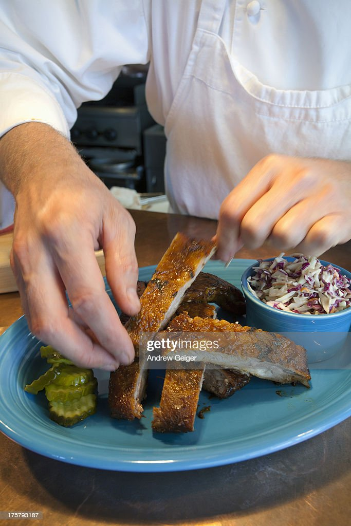 Chef arranging ribs on blue plate. : Stock Photo
