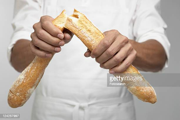 Chef breaking baguette (mid section)