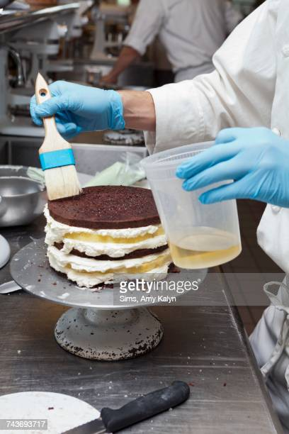 A chef brushing oil onto a layer cake