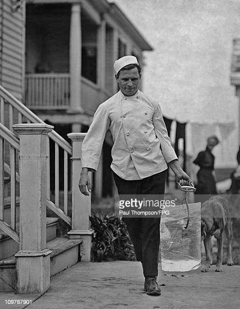 A chef carrying a block of ice circa 1920