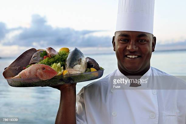 Chef Carrying Seafood Dish at Beach