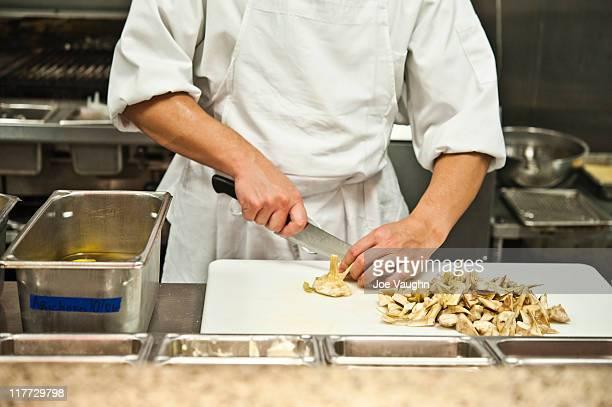 Chef chopping artichokes