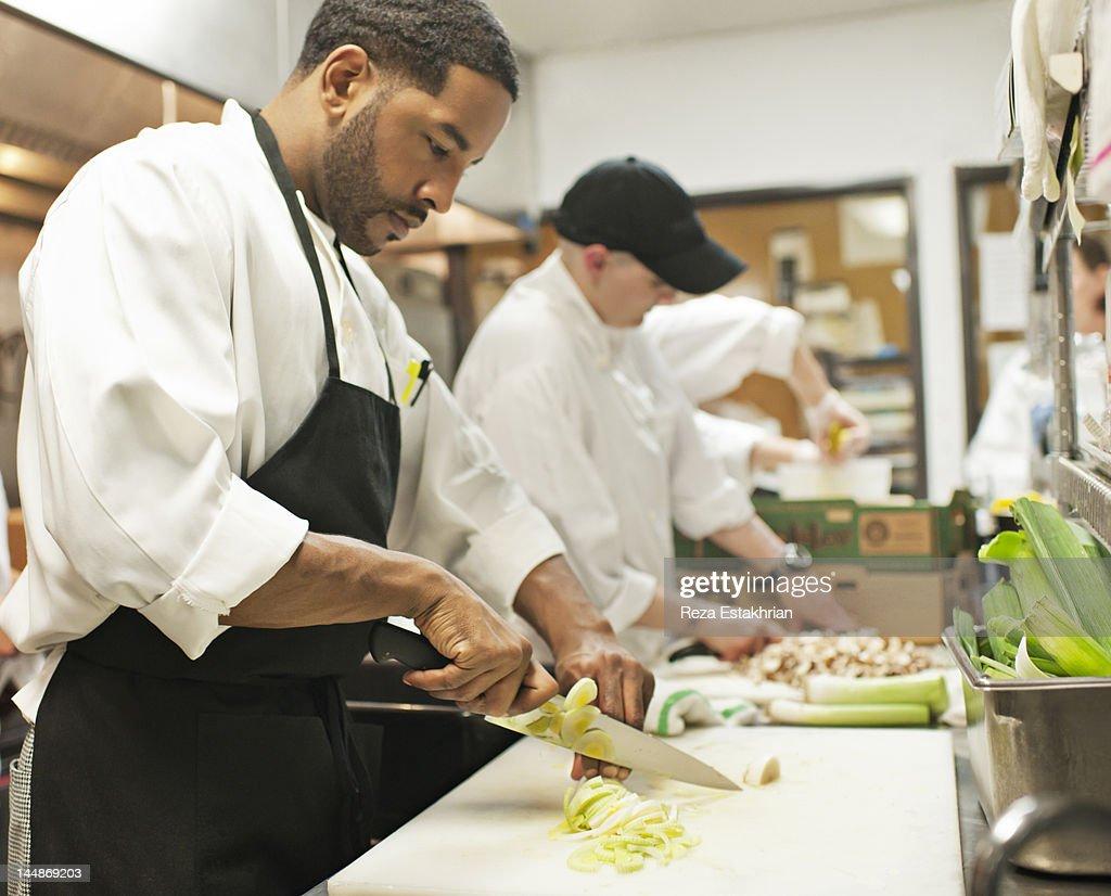 Chef chops leeks : Stock Photo